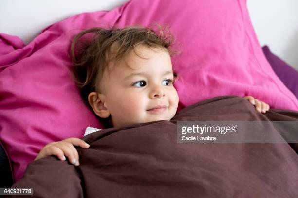 Toddler girl daydreaming in the bed