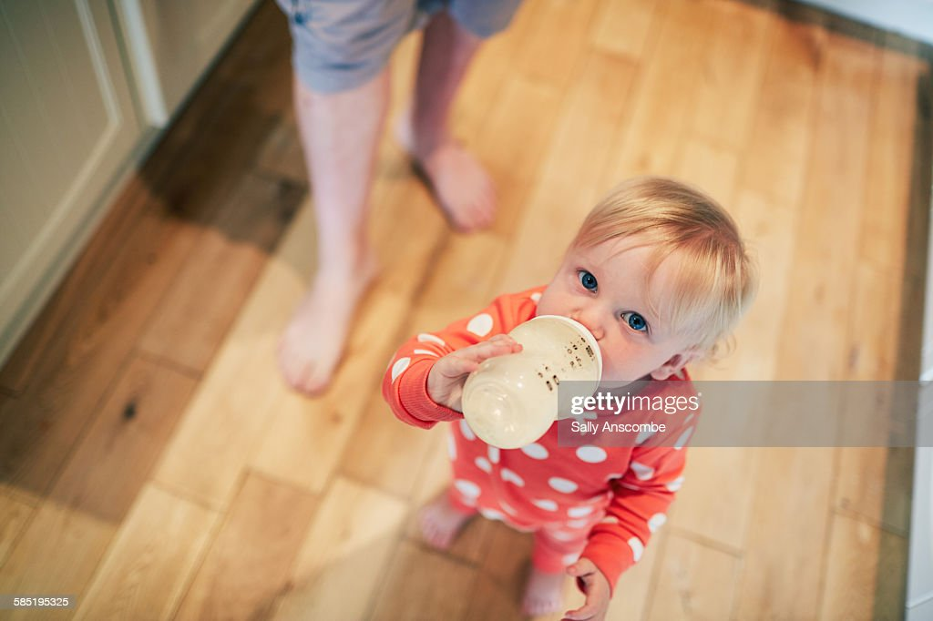 Toddler girl drinking a bottle of milk : Stock Photo