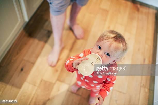 Toddler girl drinking a bottle of milk