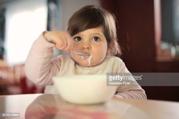 Toddler girl eating bowl of breakfast cereal