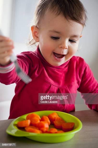Toddler girl eating carrots