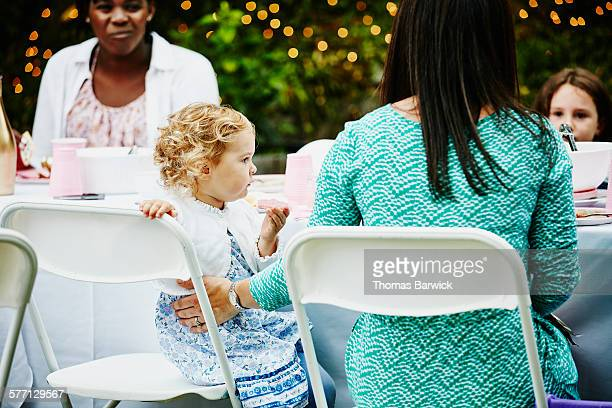 Toddler girl eating cookie sitting with mother