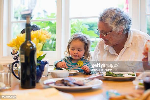 Toddler girl (2-3) eating dinner with grandmother, California, USA