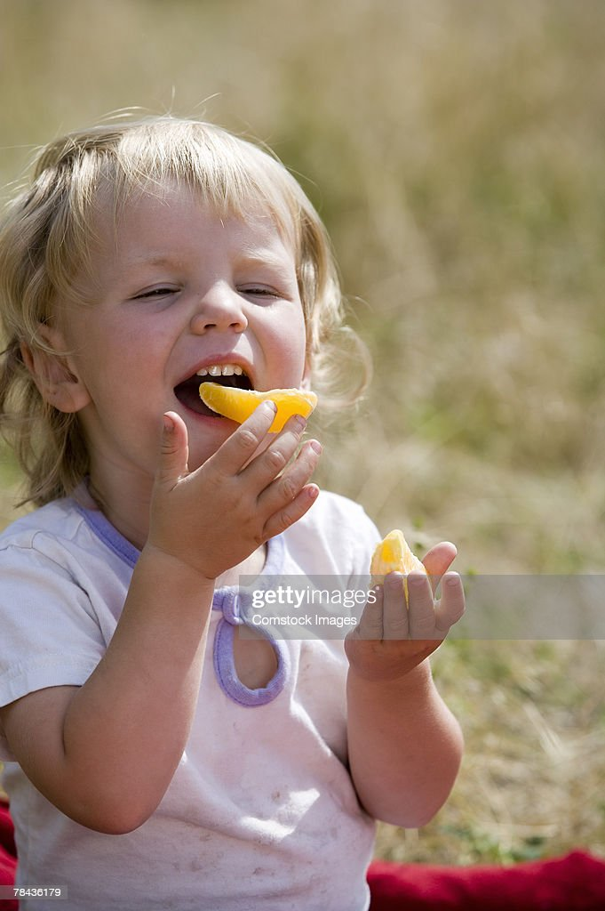 Toddler girl eating fruit : Stockfoto