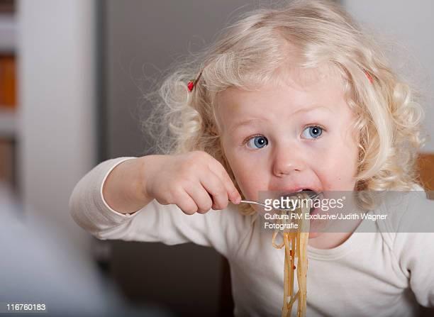 Toddler girl eating spaghetti