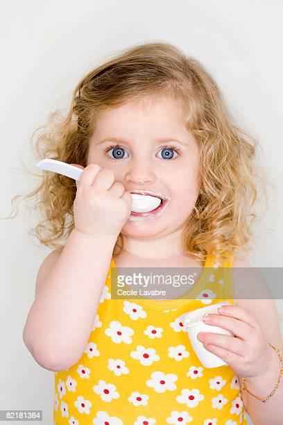 Toddler girl eating yogurt