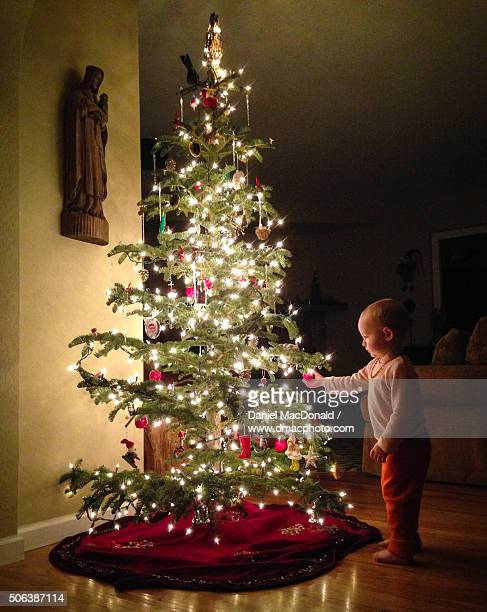 Toddler girl enchanted by Christmas tree lights and ornaments in her home