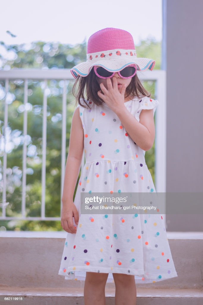 Toddler girl going out undercovered on a hot summer day : Stock Photo