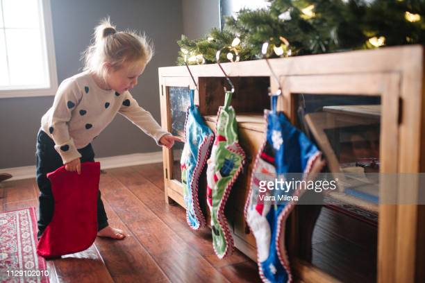 toddler girl hanging up christmas stockings - christmas stocking stock pictures, royalty-free photos & images