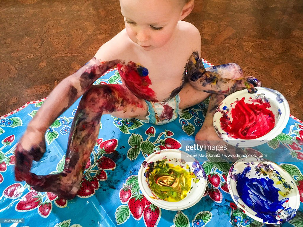 Toddler girl happily finger painting and making a mess : Stock Photo