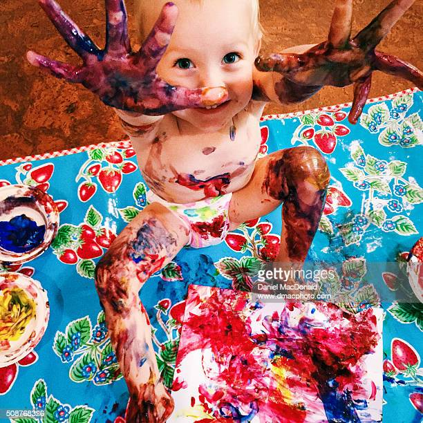 toddler girl happily finger painting and making a mess - diaper kids stock pictures, royalty-free photos & images
