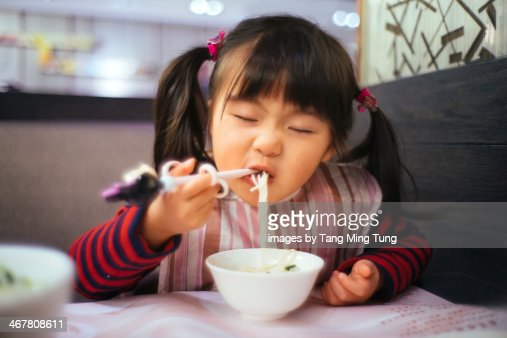 Toddler girl having noodles in restaurant