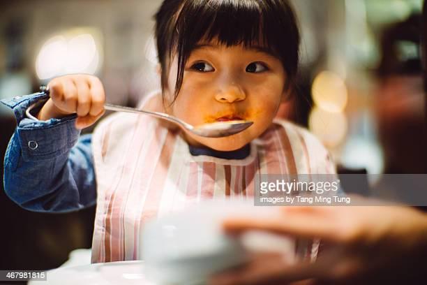 Toddler girl having soup in the restaurant