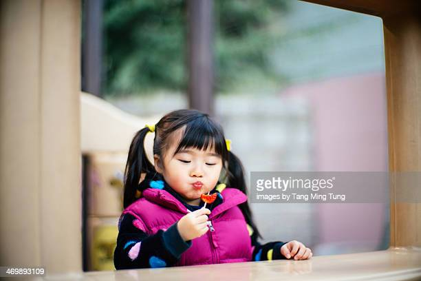Toddler girl having strawberry in playground
