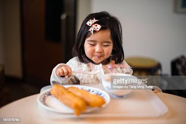 Toddler girl having traditional Chinese breakfast