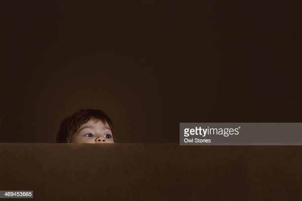 Toddler girl hiding behind a couch
