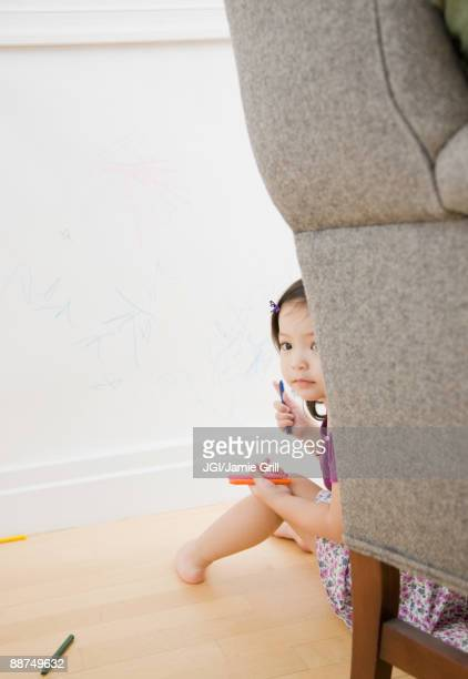 Toddler girl hiding behind chair