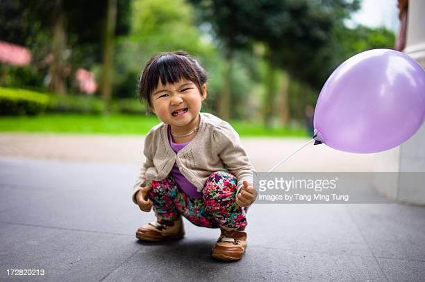 Toddler girl holding a balloon smiling joyfully