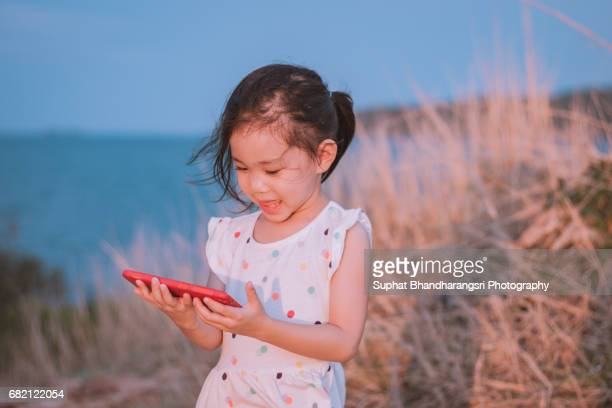 Toddler girl holding a smartphone at the hill
