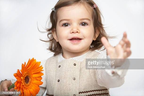 Toddler girl (18-21 months) holding flower, arm outstretched, portrait