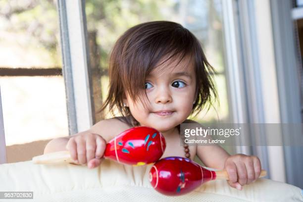 toddler girl holding maracas and looking to side