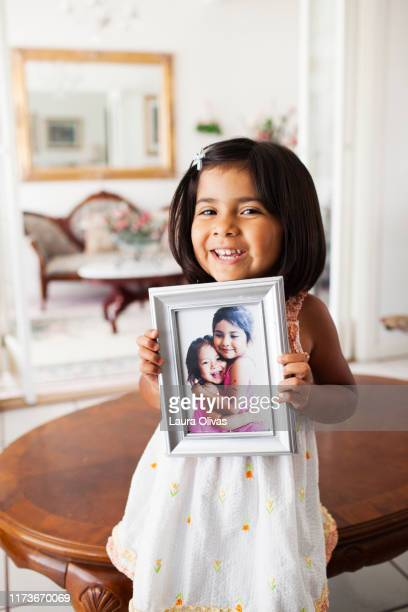 Toddler Girl Holds Photo of Her and Her Sister