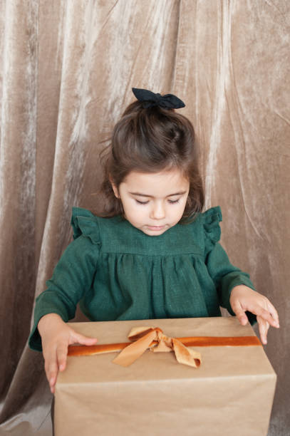A toddler girl in a green linen dress and a headband  holds a Christmas present wrapped in kraft paper and decorated with a velour ribbon and looks at it within temptation. Christmas outfit. Preparing for celebration. Festive season. Lifestyle portrait.