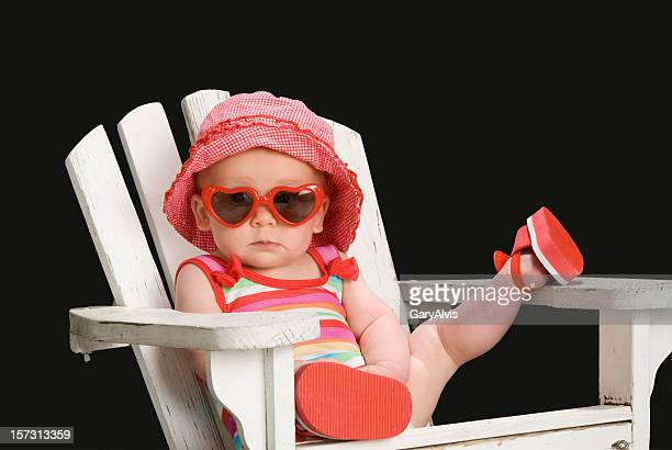 Toddler girl in Adirondack chair w/leg up,sunglasses on-total relaxation