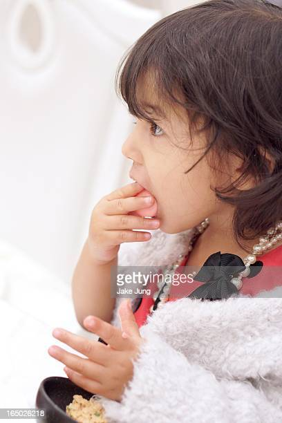Toddler girl in formal clothes eating a cookie