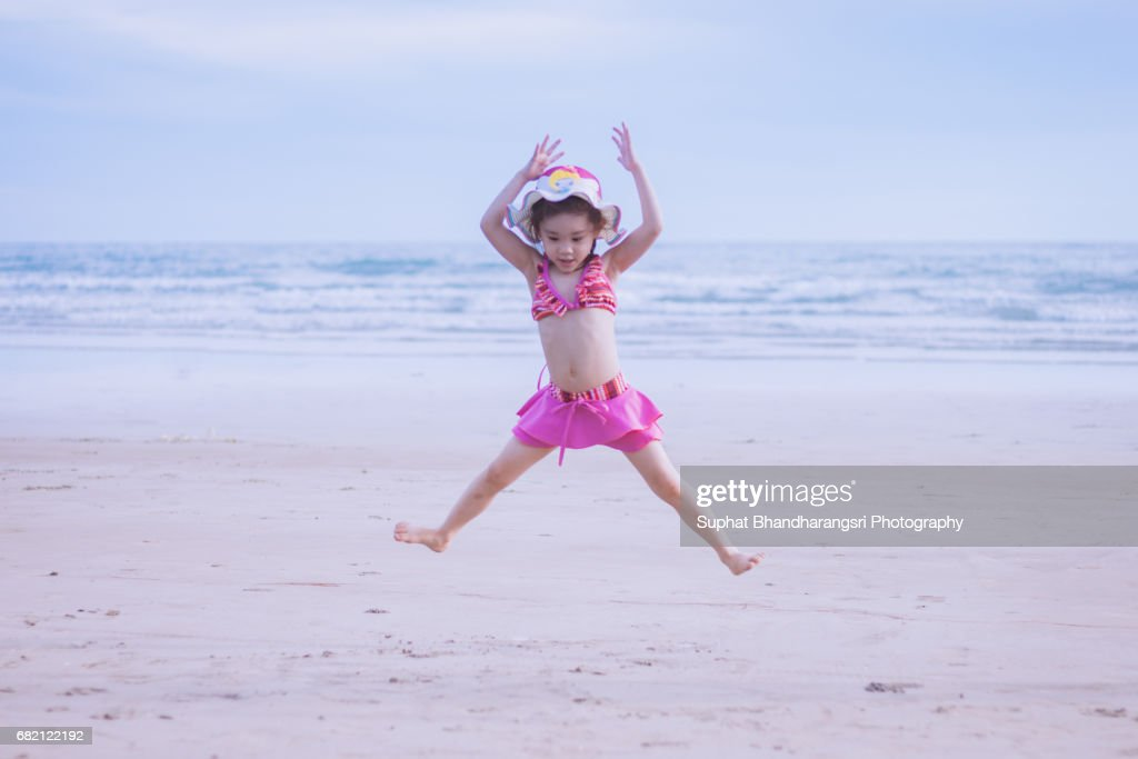 Toddler girl jumping on the beach : Stock Photo