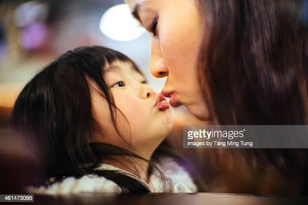 Toddler girl kissing mom's lips in the cafe