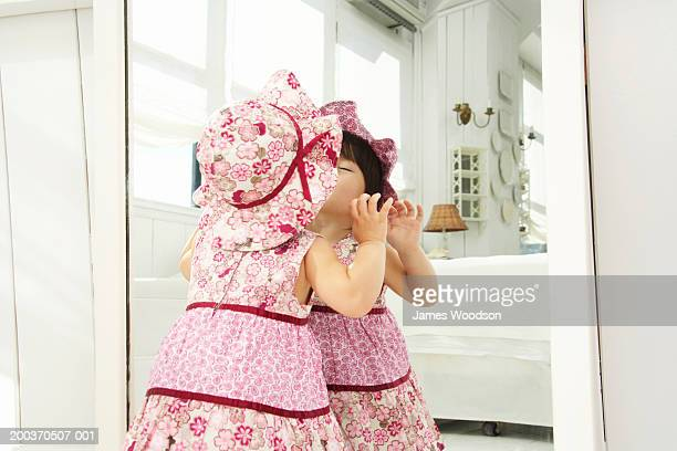 Toddler girl (21-24 months) kissing reflection in mirror, rear view