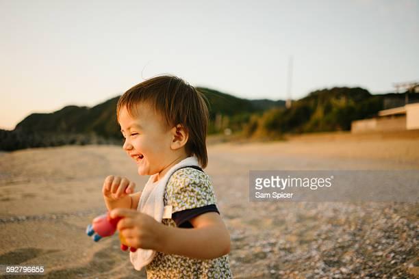 Toddler girl laughing on sunset beach