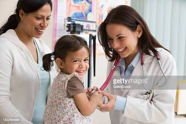 toddler girl laughing while doctor examines - paediatrician stock pictures, royalty-free photos & images