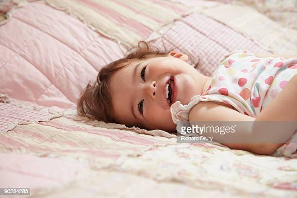 toddler girl (18 months) laying on bed laughing - richard drury stock pictures, royalty-free photos & images