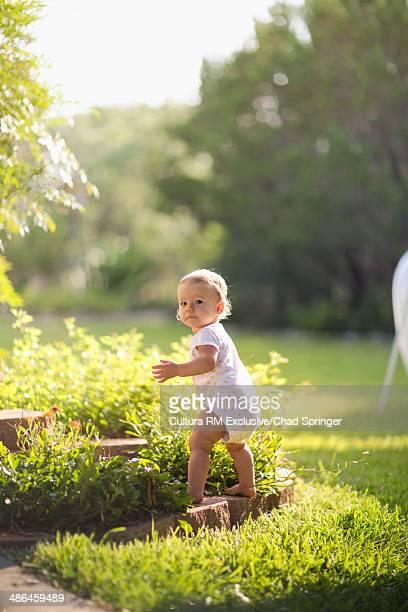 Toddler girl learning to walk in garden