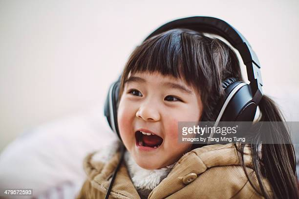 Toddler girl listening to music joyfully