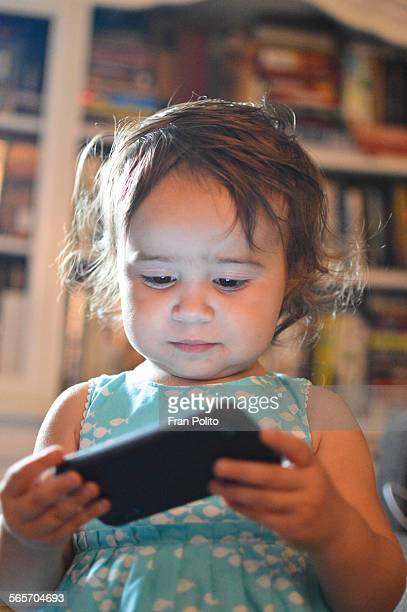 Toddler girl looking at a cell phone
