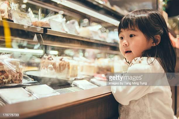 Toddler girl looking at cake window displays.