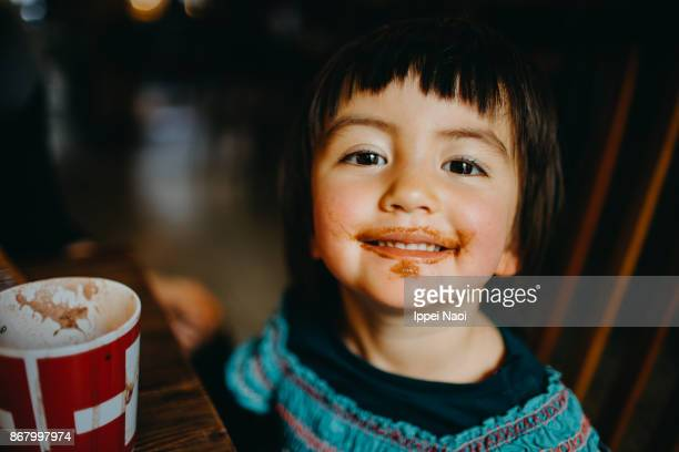 Toddler girl looking at camera with chocolate drink around her mouth