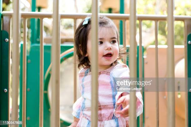 toddler girl looking happy and curious on playground