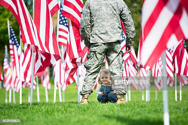 Toddler girl looking through the legs of an American Soldier