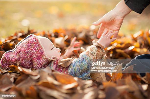 A toddler girl lying in a pile of autumn leaves gets a helping hand from her mother