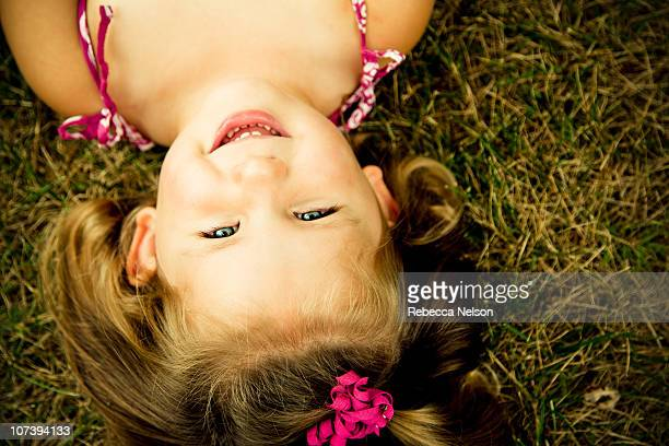 Toddler girl lying on grass, shot from above