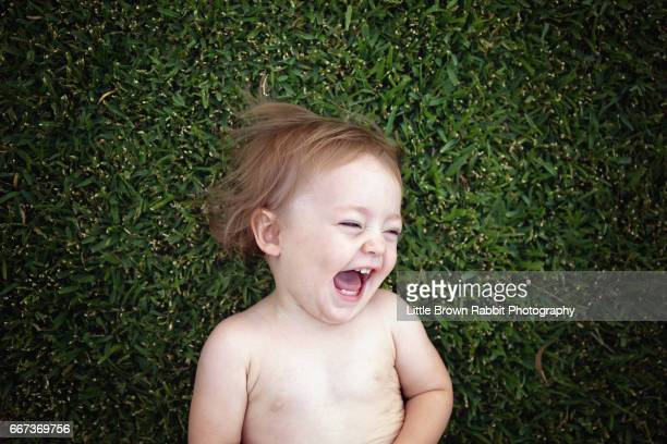 A Toddler Girl Lying on Green Grass Laughing