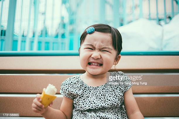 Toddler girl making funny face on a bench