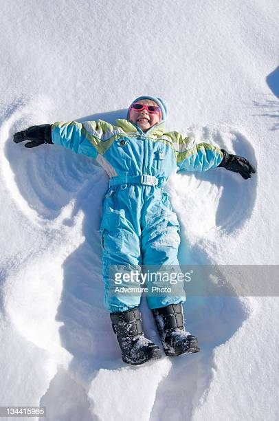toddler girl making snow angel in winter - snow angel stock photos and pictures