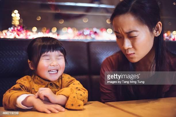 Toddler girl making wish / praying in restaurant