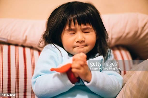 Toddler girl making wish / praying sincerely