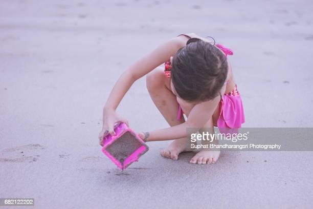 Toddler girl molding sand castle
